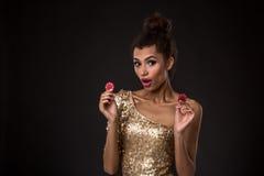 Kobiety wygranie - młoda kobieta trzyma dwa czerwonego układu scalonego w z klasą złoto sukni, grzebak as grępluje kombinację Fotografia Stock