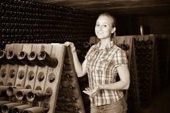 Kobiety wytwórnii win pracownika pozycja w starzeć się sekcję z butelkami Fotografia Stock
