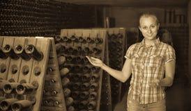 Kobiety wytwórnii win pracownika pozycja w starzeć się sekcję z butelkami Obraz Stock