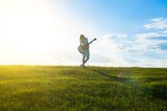 Kobiety z gitarą nad zmierzchu niebem, Obrazy Stock