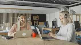 Kobiety z he?mofonami z mikrofonem opowiadaj? do siebie przy prac? zdjęcie wideo