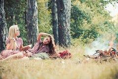 Kobiety z naturalnym makeup relaksuj? na zielonej trawie Pi?kno dziewczyny z d?ugie w?osy przy ogniskiem Mod kobiety w retro sukn zdjęcie royalty free