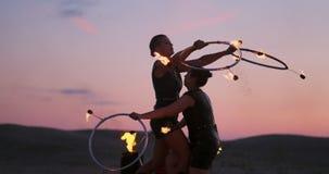 Kobiety z ogieniem przy zmierzchem na piasku tanczą sztuczki i pokazują przeciw pięknemu niebu w zwolnionym tempie zdjęcie wideo