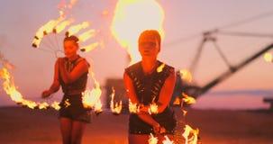 Kobiety z ogieniem przy zmierzchem na piasku tanczą sztuczki i pokazują przeciw pięknemu niebu w zwolnionym tempie zbiory