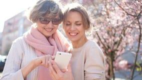 Kobiety z smartphone Wiosny portreta dwa plenerowe pogodne kobiety, matka i c?rka, matka dzie? zbiory