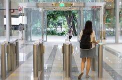 Kobiety zaludniają chodzącego od ochrony przy wejściową bramą z kluczowej karty kontrola dostępu mądrze budynkiem biurowym out zdjęcie stock