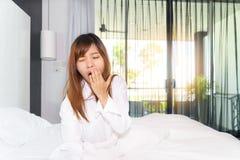 Kobiety ziewanie i rozciąganie podczas gdy budzący się up w ranku zdjęcia stock
