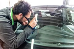 Koblenz Gerrmany 04.04.2018 man using repairing equipment to fix damaged cracked windshield at wintec company stock image