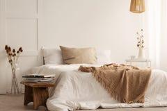 Koc na białym łóżku w naturalnym sypialni wnętrzu z roślinami i drewnianą stolec obraz royalty free