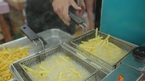 Koch bereitet Pommes-Frites in der großen Menge des Öls zu stock video