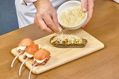 Koch besprühen mit Käse angefüllter Aubergine Lizenzfreie Stockbilder