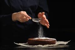 Koch besprüht Puderzucker auf Schokoladenkuchen stockbilder