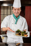 Koch demonstriert seine Teller Stockfotos