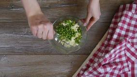 Koch, der grüne Erbsen dem Salat hinzufügt stock footage