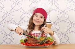 Koch des kleinen Mädchens, der großen Truthahntrommelstock isst Stockbild