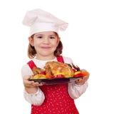 Koch des kleinen Mädchens, der Huhn anhält Stockfotografie