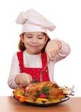 Koch des kleinen Mädchens essen Huhn Stockfotos