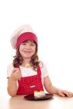 Koch des kleinen Mädchens essen Kuchen Stockbilder