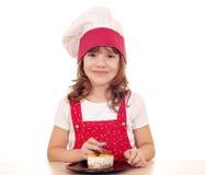 Koch des kleinen Mädchens essen Kuchen Lizenzfreie Stockfotos