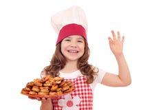 Koch des kleinen Mädchens mit bruschette und okayhand unterzeichnen Stockfotografie