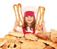 Koch des kleinen Mädchens mit Gebäck und Broten Lizenzfreie Stockfotos