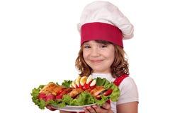 Koch des kleinen Mädchens mit gebratenem Hühnerfleisch und -salat Lizenzfreies Stockbild