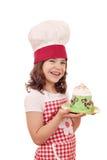 Koch des kleinen Mädchens mit großem kleinem Kuchen Stockfotografie