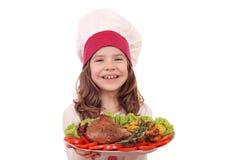 Koch des kleinen Mädchens mit großem Truthahntrommelstock und -gemüse Stockfotografie