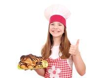Koch des kleinen Mädchens mit Hörnchen und dem Daumen oben Stockbild