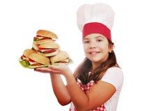 Koch des kleinen Mädchens mit Hamburgern auf Platte Lizenzfreies Stockbild