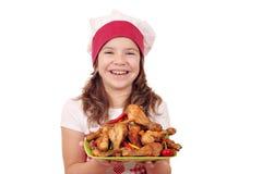 Koch des kleinen Mädchens mit Huhntrommelstock Stockbilder