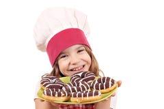Koch des kleinen Mädchens mit köstlichen Schokoladenschaumgummiringen Stockbild