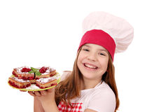 Koch des kleinen Mädchens mit Kirschtorte auf Platte Stockbilder