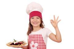 Koch des kleinen Mädchens mit Krepps und okayhand unterzeichnen Lizenzfreie Stockfotografie