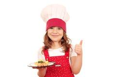 Koch des kleinen Mädchens mit Lachsen und dem Daumen oben Lizenzfreie Stockbilder