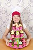 Koch des kleinen Mädchens mit Muffinnachtisch Stockbilder
