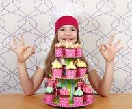 Koch des kleinen Mädchens mit Muffins und der okayhand singt Stockfotos