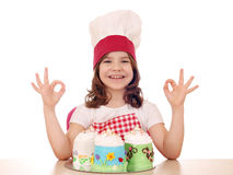 Koch des kleinen Mädchens mit süßem Kuchen und okayhand unterzeichnen Stockbild