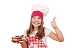 Koch des kleinen Mädchens mit selbst gemachten Torte und dem Daumen oben Lizenzfreies Stockbild