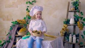 Koch des kleinen Mädchens wirft die Muffins und sitzt in der Küche stock footage