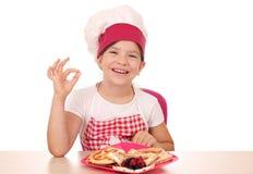 Koch des kleinen M?dchens mit Bonbonkrepps und okayhand unterzeichnen lizenzfreie stockfotos