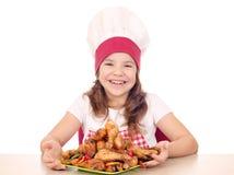 Koch des kleinen Mädchens mit gebratenen Hühnertrommelstöcken auf Platte Lizenzfreie Stockbilder
