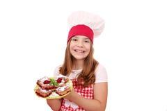 Koch des kleinen Mädchens mit selbst gemachter Torte Stockbilder
