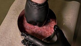 Koch macht Fleischmedaillons für Burger Chef in den schwarzen Lebensmittelhandschuhen macht Kotelett Koteletts werden im Stahlrin stock footage