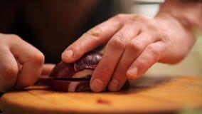 Koch schneidet die Zwiebel auf dem Schreibtisch stock footage