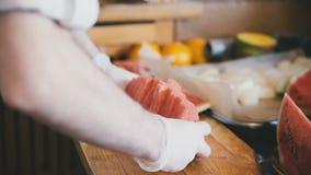 Koch schneidet eine Wassermelone mit einem Messer stock video footage