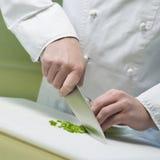 Koch schneidet Gemüse Stockfotografie