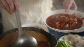 Koch setzt die Platte in den fertigen Teller ein Traditioneller ukrainischer Borschtschteller stock footage