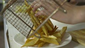 Koch setzt Pommes-Frites gebratene Kartoffeln auf eine Platte mit Fleischklöschen an Hand in das Esszimmer ein stock video