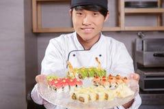 Koch zeigt einen Sushisatz Stockfotografie